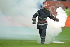 Ο πυροσβέστης αφαιρεί τις φλόγες από την πίσσα ποδοσφαίρου Στοκ φωτογραφία με δικαίωμα ελεύθερης χρήσης