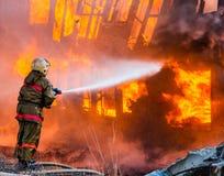 Ο πυροσβέστης εξαφανίζει μια πυρκαγιά Στοκ Φωτογραφία