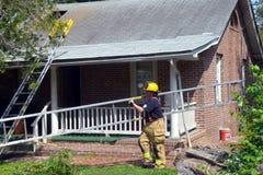 Ο πυροσβέστης φέρνει μια σκάλα έξω από ένα σπίτι στοκ εικόνες