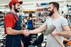Ο πωλητής δίνει το γενειοφόρο νέο γιγαντιαίο σφυρί πελατών στο κατάστημα εργαλείων δύναμης άτομα χεριών που τινάζουν δύο Στοκ εικόνες με δικαίωμα ελεύθερης χρήσης