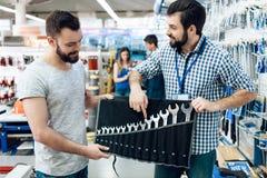 Ο πωλητής παρουσιάζει γενειοφόρο σύνολο πελατών γαλλικών κλειδιών στο κατάστημα εργαλείων δύναμης στοκ φωτογραφία