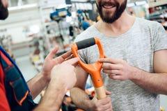 Ο πωλητής παρουσιάζει ζεύγος του νέου showel πελατών στο κατάστημα εργαλείων δύναμης στοκ φωτογραφία