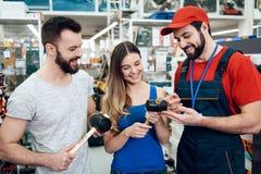 Ο πωλητής παρουσιάζει ζεύγος των νέων λαστιχένιων σφυριών πελατών στο κατάστημα εργαλείων δύναμης στοκ φωτογραφία με δικαίωμα ελεύθερης χρήσης