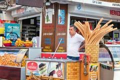 Ο πωλητής του τουρκικού παγωτού είναι πίσω από τα αντίθετα περιμένοντας FO Στοκ Εικόνες