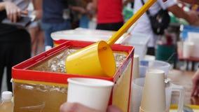 Ο πωλητής χύνει το παγωμένο τσάι στην τοπική αγορά closeup 4K φιλμ μικρού μήκους