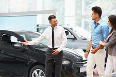 Ο πωλητής Ð ¡ AR προσκαλεί τους πελάτες στην αίθουσα εκθέσεως Στοκ Εικόνα