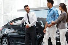 Ο πωλητής αυτοκινήτων προσκαλεί τους πελάτες στην αίθουσα εκθέσεως Στοκ Εικόνες