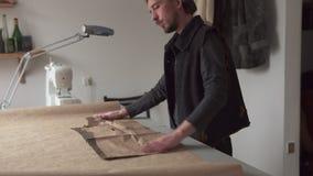 Ο ράφτης ατόμων δημιουργεί το σχέδιο ιματισμού εργαζόμενος στο εργαστήριο απόθεμα βίντεο