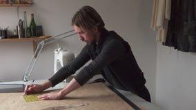 Ο ράφτης ατόμων σύρει το σχέδιο ιματισμού εργαζόμενος στο εργαστήριο απόθεμα βίντεο
