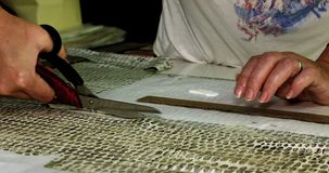 Ο ράφτης κόβει το ύφασμα με το μεγάλο διαμορφωμένο ψαλίδι υφαντικό προϊόν Κλείστε - επάνω των χεριών και του ψαλιδιού φιλμ μικρού μήκους