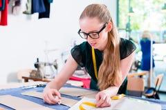 Ο ράφτης μεταφέρει το σχέδιο του σχεδίου μόδας στο ύφασμα Στοκ Φωτογραφία
