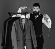 Ο ράφτης με το σοβαρό πρόσωπο κρατά τη μέτρηση της ταινίας κοντά στα σακάκια συνήθειας Στοκ φωτογραφία με δικαίωμα ελεύθερης χρήσης