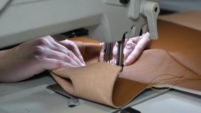 Ο ράφτης ράβει το καφετί δέρμα στο ράψιμο του εργαστηρίου δύο βελόνες της ράβοντας μηχανής κινούνται γρήγορα πάνω-κάτω, κινηματογ απόθεμα βίντεο