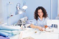 Ο ράφτης της Νίκαιας κάθεται στο γραφείο και σχετικά με το ρόδινο νήμα Στοκ φωτογραφία με δικαίωμα ελεύθερης χρήσης