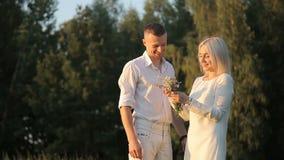 Ο ρομαντικός τύπος δίνει σε ένα κορίτσι μια αγροτική ανθοδέσμη των άγριων λουλουδιών απόθεμα βίντεο