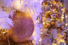 Ο ρόδινος-χρυσός ακτινοβολεί διαμορφωμένη σφαίρα διακόσμηση Χριστουγέννων με το θολωμένο λαμπιρίζοντας χριστουγεννιάτικο δέντρο σ Στοκ εικόνες με δικαίωμα ελεύθερης χρήσης