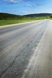 Ο δρόμος ασφάλτου πηγαίνει στην απόσταση και εξαφανίζεται στα ξύλα Στοκ φωτογραφία με δικαίωμα ελεύθερης χρήσης