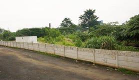Ο δρόμος και τα δέντρα που χωρίζονται από τη φωτογραφία τοίχων τσιμέντου που λαμβάνεται στο Σεμαράνγκ Ινδονησία Στοκ φωτογραφία με δικαίωμα ελεύθερης χρήσης