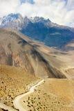 Ο δρόμος στα βουνά Himalayan στο υπόβαθρο των χιονωδών αιχμών και του μπλε ουρανού με τα σύννεφα Νεπάλ Ανώτερο μάστανγκ ` βασίλει Στοκ Εικόνες