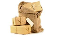 Ο σάκος ή η θέση ταχυδρομείου τοποθετεί σε σάκκο με διάφορες τυλιγμένες συσκευασίες, που απομονώνονται στο λευκό στοκ φωτογραφία