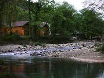 Ο σαφής κολπίσκος στο δάσος, το ξύλινο σπίτι δίπλα στον κολπίσκο στοκ εικόνα