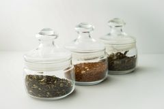 ο σαφής κύκλος βάζων γυαλιού διόγκωσε χαμηλά για το τσάι με το καπάκι στο άσπρο υπόβαθρο με το μαύρο και πράσινο τσάι κρέμας μέσα στοκ εικόνες