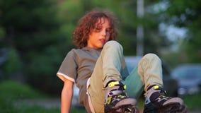 Ο σγουρός έφηβος βάζει στους κυλίνδρους στο πάρκο Μαθητών, ηλιοβασίλεμα απόθεμα βίντεο