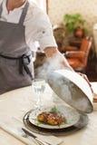 Ο σερβιτόρος ανοίγει το καπάκι του πιάτου στοκ εικόνες με δικαίωμα ελεύθερης χρήσης