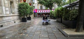 Ο σερβιτόρος καφέδων παίρνει ένα σπάσιμο στο plaza του Παρισιού, ελέγχει το τηλέφωνο κυττάρων Στοκ Εικόνες