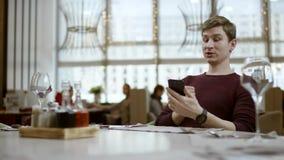 Το άτομο κάθεται στον πίνακα στο εστιατόριο, κοιτάζει σε έναν λογαριασμό και κάνει την πληρωμή από την κάρτα Ο σερβιτόρος κρατά τ φιλμ μικρού μήκους