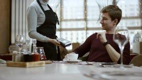 Το άτομο κάθεται στον πίνακα στο εστιατόριο, κοιτάζει σε έναν λογαριασμό και κάνει την πληρωμή από την κάρτα Ο σερβιτόρος κρατά τ απόθεμα βίντεο
