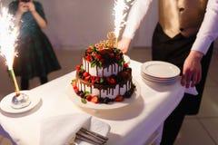 Ο σερβιτόρος με μορφή του εστιατορίου βγάζει ένα όμορφο κέικ γαμήλιου γιαουρτιού με την αγάπη επιγραφής και τις καίγοντας πυρκαγι στοκ εικόνες με δικαίωμα ελεύθερης χρήσης