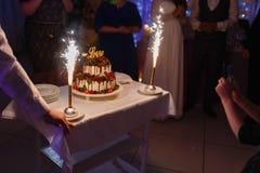 Ο σερβιτόρος με μορφή του εστιατορίου βγάζει ένα όμορφο κέικ γαμήλιου γιαουρτιού με την αγάπη επιγραφής και τις καίγοντας πυρκαγι στοκ εικόνες