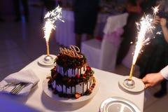Ο σερβιτόρος με μορφή του εστιατορίου βγάζει ένα όμορφο κέικ γαμήλιου γιαουρτιού με την αγάπη επιγραφής και τις καίγοντας πυρκαγι στοκ εικόνα