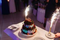 Ο σερβιτόρος με μορφή του εστιατορίου βγάζει ένα όμορφο κέικ γαμήλιου γιαουρτιού με την αγάπη επιγραφής και τις καίγοντας πυρκαγι στοκ φωτογραφία