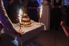 Ο σερβιτόρος με μορφή του εστιατορίου βγάζει ένα όμορφο κέικ γαμήλιου γιαουρτιού με την αγάπη επιγραφής και τις καίγοντας πυρκαγι στοκ φωτογραφίες
