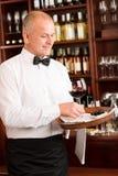 Ο σερβιτόρος ράβδων κρασιού ώριμος εξυπηρετεί το εστιατόριο γυαλιού στοκ εικόνες