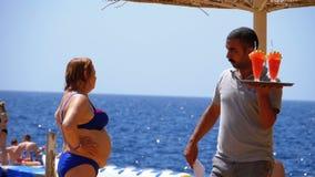 Ο σερβιτόρος στην παραλία φέρνει τους εξωτικούς φρέσκους χυμούς και τα κοκτέιλ σε έναν δίσκο στην Αίγυπτο o απόθεμα βίντεο