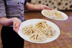 Ο σερβιτόρος φέρνει ένα πιάτο του khinkali Στοκ Φωτογραφίες