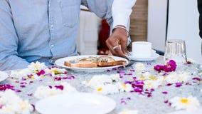 Ο σερβιτόρος φέρνει το πρόγευμα σε μια συνεδρίαση ζευγών στον πίνακα που καλύπτεται με τα λουλούδια στοκ εικόνες