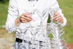 Ο σερβιτόρος χτίζει μια πυραμίδα των γυαλιών για τη σαμπάνια Στοκ Εικόνες