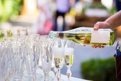 Ο σερβιτόρος χύνει τη σαμπάνια σε ένα ποτήρι Κενά γυαλιά στο whi Στοκ φωτογραφία με δικαίωμα ελεύθερης χρήσης