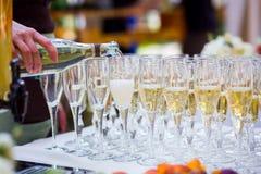 Ο σερβιτόρος χύνει τη σαμπάνια σε ένα ποτήρι Κενά γυαλιά στο whi Στοκ φωτογραφίες με δικαίωμα ελεύθερης χρήσης