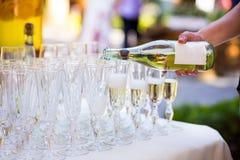 Ο σερβιτόρος χύνει τη σαμπάνια σε ένα ποτήρι Κενά γυαλιά στο whi Στοκ Εικόνα
