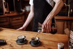Ο σερβιτόρος χύνει τον επίγειο καφέ στα φλυτζάνια για τους επισκέπτες στοκ φωτογραφία