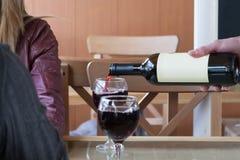 Ο σερβιτόρος χύνει το κρασί στο ποτήρι Στοκ Εικόνες