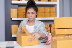 Ο σε απευθείας σύνδεση επιχειρηματίας γυναικών που χρησιμοποιεί την ταινία στο box οφφηθε δεμάτων συσκευασίας στο σπίτι, προετοιμ στοκ φωτογραφία με δικαίωμα ελεύθερης χρήσης
