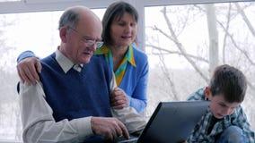 Ο σε απευθείας σύνδεση ο οικογενειακοί ελεύθερος χρόνος, το grandma και παππούς αγορών με τον εγγονό κάθονται στο διαδίκτυο μέσω  απόθεμα βίντεο