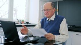 Ο σε απευθείας σύνδεση ψωνίζοντας συνταξιούχος εργάζεται σε Διαδίκτυο στον υπολογιστή με τα έγγραφα στο Υπουργείο Εσωτερικών απόθεμα βίντεο