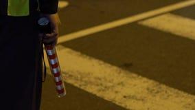 Ο σε αργή κίνηση αστυνομικός ρυθμίζει το χρησιμοποιημένο λάμποντας αυτοκίνητα ελαφρύ ραβδί μετακίνησης φιλμ μικρού μήκους